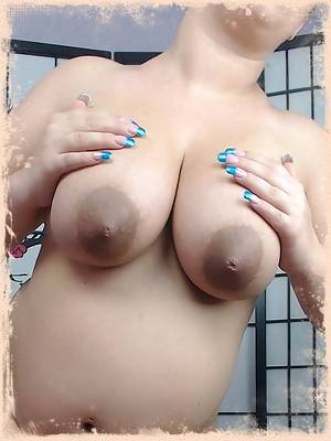 Curvy pregnant porn star Georgia Peach shows off her big swollen belly as she lifts her pink dress