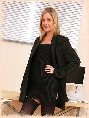 Blonde Nikki wearing an all black secretary suit.